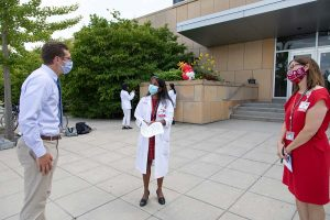 Three people speaking to each other while six feet apart, they are wearing surgical style masks