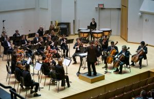An image of the orchestra members and conductor playing onstage during a performance.