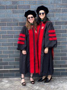 two women in academic regalia and sunglasses smile at camera