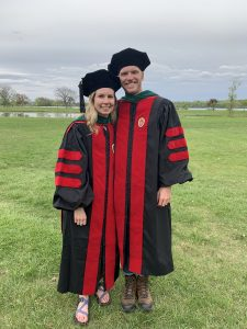 two medical student graduates in cap and gown