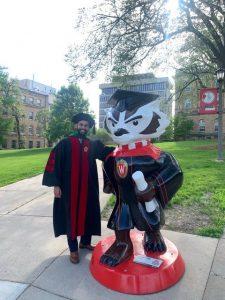 man in academic regalia posing near plastic large replica of wisconsin badger mascot