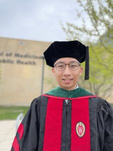man in tam and gown smiling at camera
